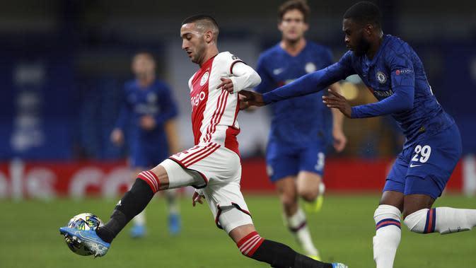 Gelandang Ajax, Hakim Ziyech mengontrol bola dari kawalan bek Chelsea, Fikayo Tomori pada pertandingan lanjutan Grup H Liga Champions di Stamford Bridge, London (5/11/2019). Chelsea bermain imbang 4-4 atas Ajax. (AP Photo/Frank Augstein)