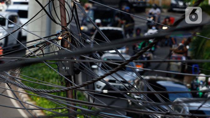 Kendaraan melintas di bawah kabel listrik dan kabel optik yang terlihat semrawut di kawasan Taman Puring, Jakarta, Jumat (3/7/2020). Kesemrawutan kabel ini sering terlihat di sejumlah kawasan Jakarta yang menyebabkan pemandangan kurang enak untuk dilihat. (Liputan6.com/Johan Tallo)
