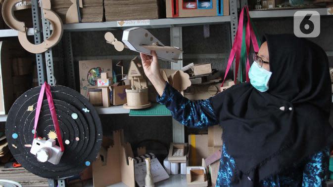 Perajin menunjukkan mainan dari kardus di Rumah Mainan Kardus, Depok, Jawa Barat, Kamis (1/10/2020). Mainan berbahan baku kardus tersebut dijual dengan harga Ro 50 ribu hingga Rp 1.200.000 tergantung besar kecil ukuranya dan tingkat kesulitan. (merdeka.com/Arie Basuki)