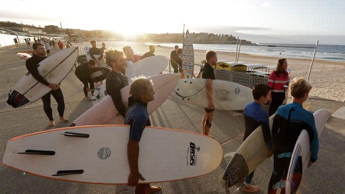 Peselancar menunggu petugas membuka Pantai Bondi saat pembatasan sosial mulai dilonggarkan di Sydney, Selasa, (28/4/2020). Australia mencatat penurunan Covid-19 secara drastis. Sejumlah pembatasan sosial mulai dilonggarkan. Salah satunya pembukaan kembali Pantai Bondi. (AP Photo/Rick Rycroft)