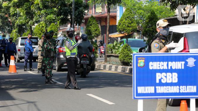 Petugas mengatur lalu lintas pada hari pertama PSBB di jalur check point Jalan Ir. H Juanda, Ciputat, Tangerang Selatan, Sabtu (18/4/2020). Peraturan tentang PSBB diteken oleh Gubernur Banten melalui Pergub No.16 Tahun 2020. (Liputan6.com/Fery Pradolo)