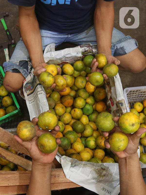 Pedagang memlilih buah jeruk di pasar induk Kramat Jati, blok buah di Jakarta, Minggu (2/2/2020). Produksi lokal dinilai perlu digenjot untuk meredam impor buah tropis yang masih berlangsung sampai saat ini. (Liputan6.com/Herman Zakharia)