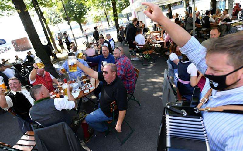 People attend a barrel tapping at a beer garden near Theresienwiese, Munich - REUTERS