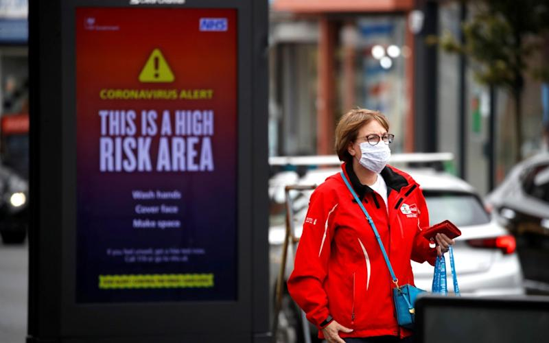 A woman wearing a protective mask walks past a warning sign in Manchester, as the city and the surrounding area faces local restrictions in an effort to avoid a local lockdown being forced upon the area, amid the coronavirus disease. - Phil Noble/Reuters
