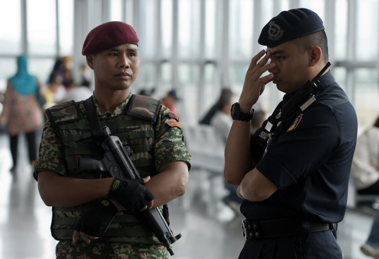 Malaysian military and police stand guard at Kuala Lumpur International Airport on March 16, 2014
