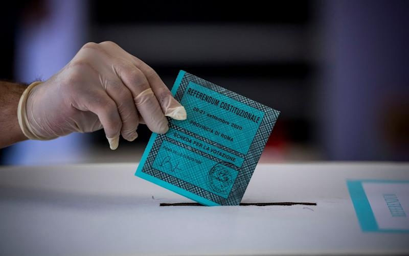 Italians voted in a referendum, and regional elections, with Covid-19 safety measures, like wearing gloves, in place - Getty Images