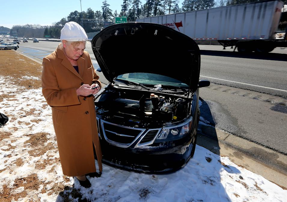Ann Batsun sends a text message as she waits for her car to be started on Interstate 75 in Atlanta, Thursday, Jan. 30, 2014. Batsun had to leave her car on the roadside after being stranded in Tuesday's winter storm. (AP Photo/John Bazemore)