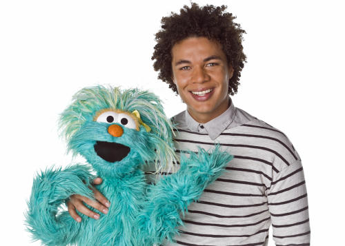 """This April 2013 photo released by Sesame Workshop shows Puerto Rican actor Ismael Cruz Cordova, 26, of """"Sesame Street,"""" posing with muppet Rosita in New York. Cruz plays Mando, a young Latino writer who interacts with the puppets and also loves technology. (AP Photo/Sesame Workshop, Gil Vaknin)"""