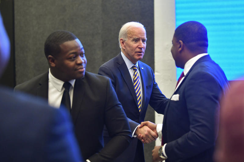 FILE - In this Nov. 21, 2019, file photo,  Democratice presidential candidate former Vice President Joe Biden is greeted by Fayetteville (N.C.) Mayor Mitch Colvin, right, after talking to Talladega (Ala.) Nayor Timothy Ragland, left, as he visits with an assembly of Southern black mayors in Atlanta. Biden is leading the most diverse presidential field in history among black voters. (AP Photo/John Amis, File)