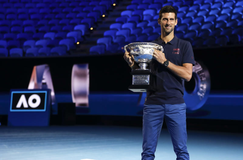 Defending men's singles champion Serbia's Novak Djokovic holds the Norman Brookes Challenge Cup during the official draw ceremony on Margaret Court Arena ahead of the Australian Open tennis championship in Melbourne, Australia, Thursday, Jan. 16, 2020. (AP Photo/Mark Baker)