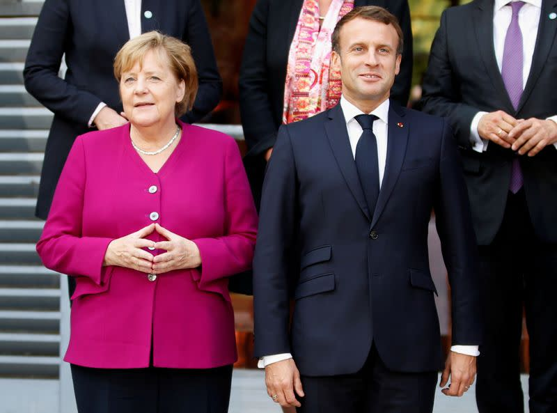 FILE PHOTO: French President Emmanuel Macron and German Chancellor Angela Merkel pose for a family photo during a joint Franco-German cabinet meeting in Toulouse