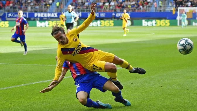 Gelandang Barcelona, Antoine Griezmann, terjatuh saat berusaha melewati pemain Eibar pada laga La Liga 2019 di Stadion Ipurua, Sabtu (19/10). Barcelona menang 3-0 atas Eibar. (AP/Alvaro Barrientos)