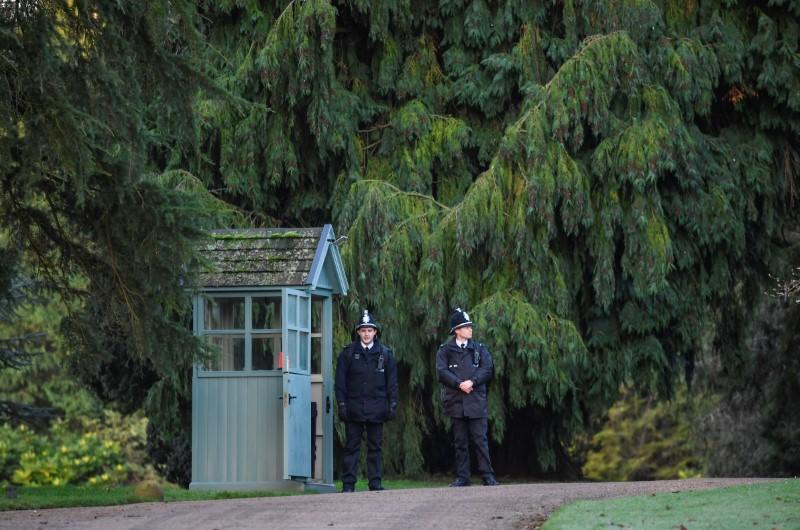 Police officers stand guard at the entrance to theSandringhamEstateineasternEngland