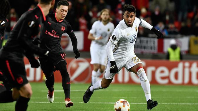 Pemain Arsenal Mesut Ozil berebut bola dengan pemain Ostersunds Brwa Nouri pada laga leg pertama babak 32 besar Liga Europa di Jamtkraft Arena, Jumat (16/2). Arsenal memetik kemenangan tandang 3-0 atas Ostersunds. (Robert Henriksson/TT News Agency via AP)