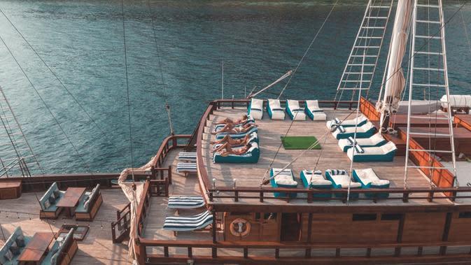 Penikmat kapal pinisi, The Maj Oceanic saat berjemur. Di samping ragam fasilitas menarik di atas kapal, pelancong juga bisa menikmati berbagai agenda menarik selama melakukan pelayaran. Beberapa di antaranya adalah snorkeling, diving, dan kayaking. (dok. The Maj Oceanic)