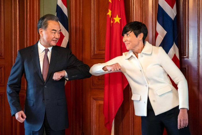 Wang Yi bumps elbows with Norway's foreign minister Ine Erisen Soreide in Oslo last month.