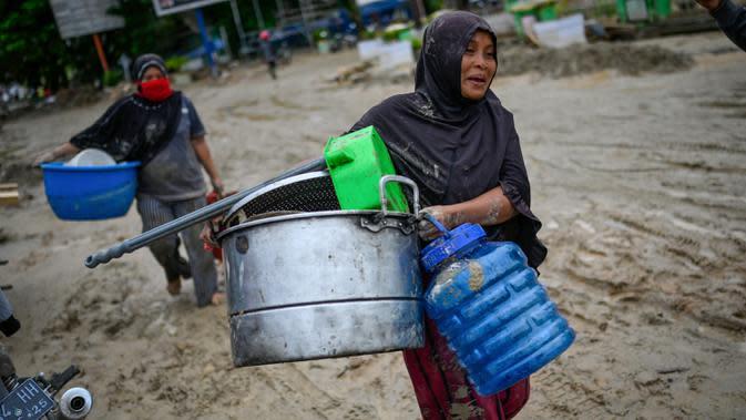 Penduduk desa membawa barang-barang dari rumah mereka sebelum mengungsi setelah banjir bandang di Kabupaten Luwu Utara, Sulawesi Selatan, Rabu (15/7/2020). Akibat banjir bandang tersebut mengakibatkan 16 orang meninggal dunia dan ratusan rumah tertimbun lumpur. (Hariandi HAFID / AFP)