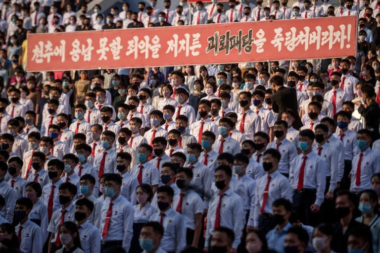 Students and youths hold a banner reading: 'Let us stamp out the South Korean puppet forces who perpetrated indelible crime!' as they attend a mass gathering in Pyongyang