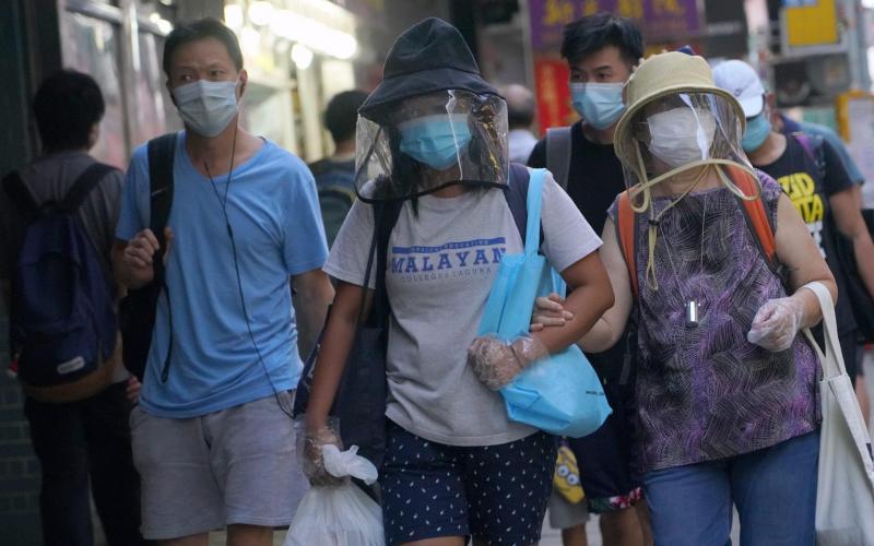 People wearing face masks walk along a street in China - China News Service