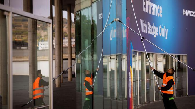 Pekerja membersihkan jendela di salah satu pintu masuk lokasi pameran Mobile World Congress (MWC) 2020 di Barcelona, Spanyol, Selasa (11/2/2020). MWC 2020 dibatalkan setelah sejumlah vendor ternama memutuskan menarik diri karena ancaman virus corona. (AP Photo/Emilio Morenatti)