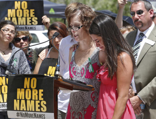 Carlee Soto, whose sister Victoria was killed in the Newtown school shooting, is comforted by Jane Dougherty, left, whose sister Mary Sherlach was also killed in the Newtown shooting, as Dougherty reads names of victims during a ceremony at Cherry Creek State Park in Aurora, Colo., on Friday, July 19, 2013. Saturday, July 20 is the anniversary of the Aurora theater shootings. (AP Photo/Ed Andrieski)