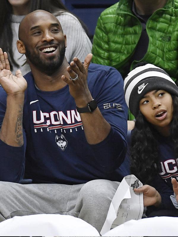 Pebasket NBA Kobe Bryant dan putrinya Gianna Bryant menonton pertandingan bola basket perguruan tinggi NCAA antara Connecticut dan Houston di Storrs, Conn pada Maret 2019. Kobe Bryant dan putrinya Gianna meninggal dalam kecelakaan helikopter di Calabasas, California. (AP Photo/Jessica Hill)