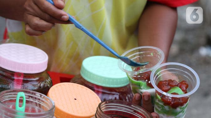 Pedagang meracik minuman untuk berbuka puasa di kawasan Bendungan Hilir, Jakarta, Sabtu (25/4/2020). Meski ditengah pandemi virus Covid-19, masyarakat masih antusias berburu penganan berbuka puasa dengan tetap menerapkan pola jaga jarak dan memakai masker. (Liputan6.com/Helmi Fithriansyah)