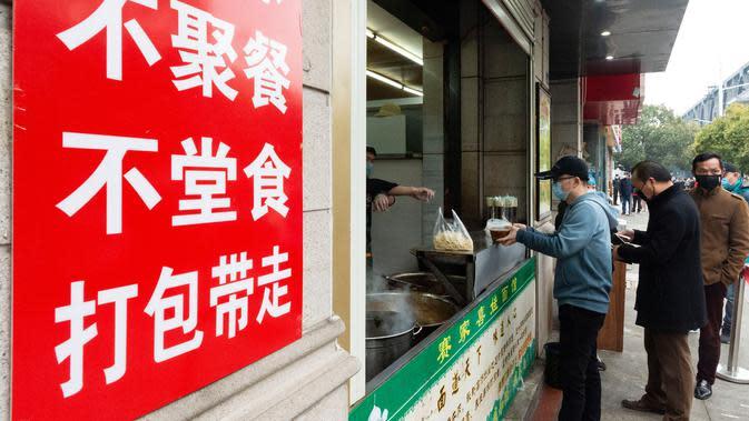 Para pelanggan mengantre untuk membeli mi sapi di sebuah restoran di Xiangyang, Provinsi Hubei, China tengah, pada 16 Maret 2020. Beberapa restoran mi sapi di Xiangyang kembali melanjutkan bisnis dengan layanan take away pada Senin (16/3). (Xinhua/Xie Jianfei)