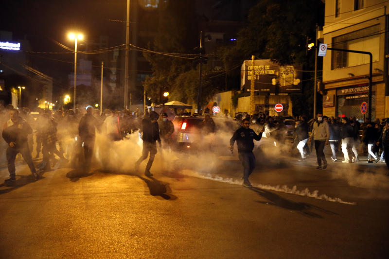 Protesters are seen surrounded by tear gas that was fired towards them by Lebanese riot police during an anti-government protest in Beirut, Lebanon, Wednesday, Dec. 4, 2019. Protesters have been holding demonstrations since Oct. 17 demanding an end to corruption and mismanagement by the political elite that has ruled the country for three decades. (AP Photo/Bilal Hussein)