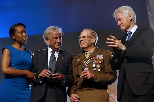 Former President Bill Clinton, right, and poet Rebecca Dupas, left, present Nobel Peace Prize laureate Elie Wiesel, a Holocaust survivor, second from left, and World War II Army veteran Scottie Ooton, a member of the 84th Infantry Division which liberated Hannover-Ahlem concentration camp, second from right, with pins marking the 20th anniversary of the United States Holocaust Memorial Museum in Washington, Monday, April 29, 2013. (AP Photo/Charles Dharapak)