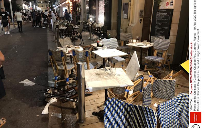 Tables and chair are upturned on Canne's Coup de Feu after crowds raced for safety - Shutterstock