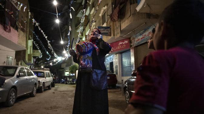Seorang mesaharati Hajja Dalal (46) membangunkan warga untuk sahur saat bulan suci Ramadan di Kairo, Mesir, Rabu (29/4/2020). Setelah salat Idul Fitri, seorang mesaharati akan mengumpulkan uang dari jalan yang dia lewati sebagai imbalan atas usahanya selama Ramadan. (AP Photo/Nariman El-Mofty)