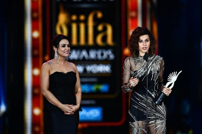 Taapsee Pannu accepts Women of the Year award as Preity Zinta looks on during IIFA award of the 18th International Indian Film Academy Festival at the MetLife Stadium in East Rutherford, New Jersey, on July 15, 2017. (Photo credit: JEWEL SAMAD/AFP via Getty Images)