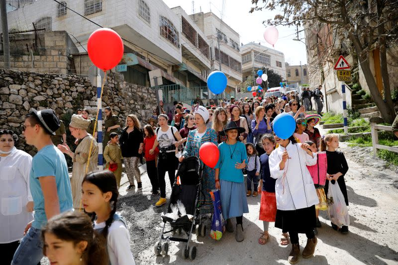 FILE PHOTO: Israeli settlers, some dressed up in costumes, take part in celebrations marking the Jewish holiday of Purim, in the Israeli-occupied West Bank city of Hebron