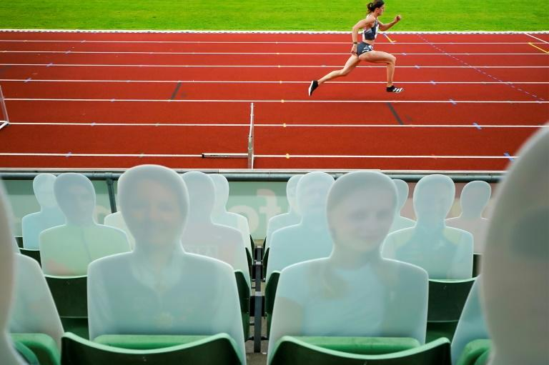 Lea Springer of Switzerland competes in the women's 300m hurdles with a background of cardboard cut outs of spectators