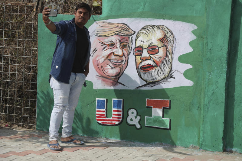 A man takes a selfie with portraits of U.S. President Donald Trump and Indian Prime Minister Narendra Modi painted on a wall ahead of Trump's visit, in Ahmadabad, India, Tuesday, Feb. 18, 2020. Trump is scheduled to visit the city during his Feb. 24-25 India trip. (AP Photo/Ajit Solanki)