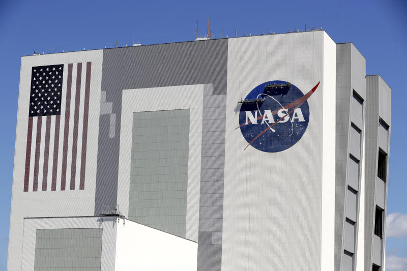 Workers near the top of the 526 ft. Vehicle Assembly Building at the Kennedy Space Center spruce up the NASA logo standing on scaffolds in Cape Canaveral, Fla., Wednesday, May 20, 2020. A SpaceX Falcon 9 rocket scheduled for May 27 will launch a Crew Dragon spacecraft on its first test flight with astronauts on-board to the International Space Station. (AP Photo/John Raoux)