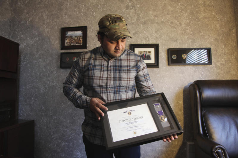 In this Monday, Dec. 16, 2019, photo, Zia Ghafoori displays the Purple Heart at his home in Charlotte, N.C., that he received while working with U.S. Forces in Afghanistan. Ghafoori was an interpreter and was wounded while fighting insurgents with U.S. Special Forces during the Battle of Shok Valley, Afghanistan. He received a Special Immigrant Visa in 2014 and is working toward becoming a U.S. citizen. (AP Photo/ Sarah Blake Morgan)