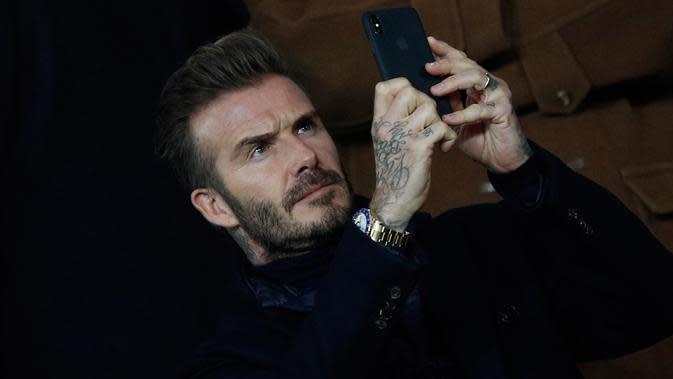 David Beckham mengambil gambar saat menonton pertandingan antara PSG dan Real Madrid di stadion Parc des Princes di Paris (6/3). David Beckham, yang pernah berkostum Madrid dan PSG juga turut hadir menonton pertandingan. (AP Photo/Christophe Ena)