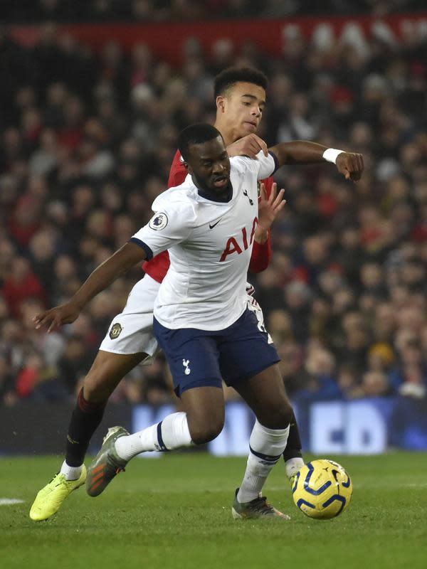 Gelandang Manchester United, Mason Greenwood berebut bola dengan pemain Tottenham Hotspur, Tanguy Ndombele pada pertandingan lanjutan Liga Inggris di Old Trafford, Rabu (4/12/2019). MU menang tipis atas Tottenham 2-1. (AP Photo/Rui Vieira)