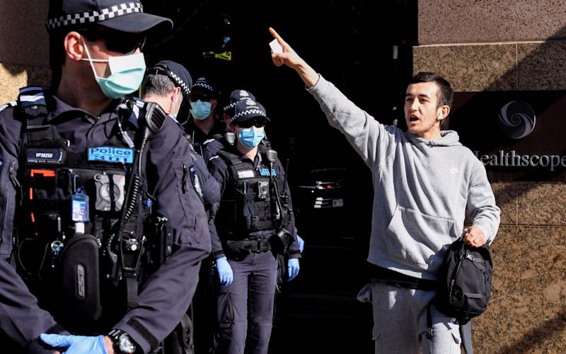 An anti-mask protester shouts at police in Melbourne