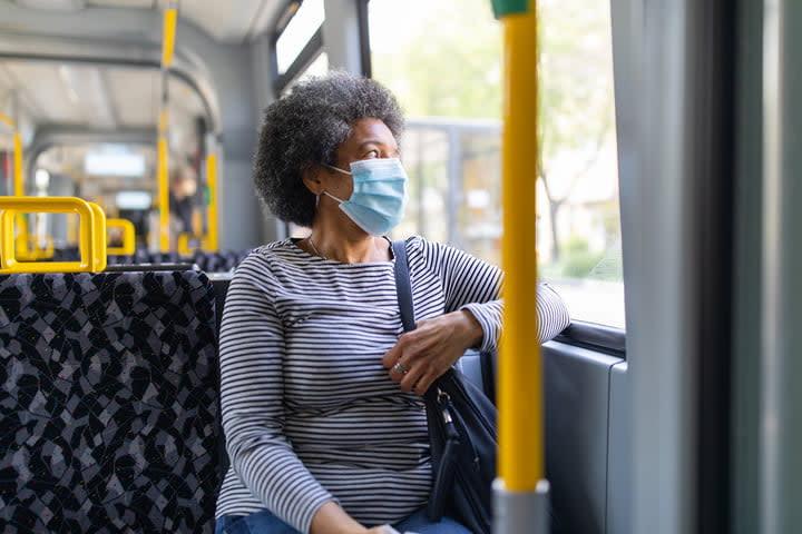 Woman wearing face mask while using public transit.