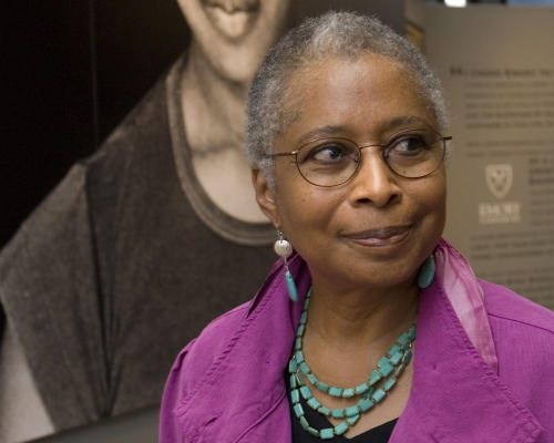 "FILE - In this April 23, 2009 file photo, Alice Walker stands in front of a picture of herself from 1974 as she tours her archives at Emory University, in Atlanta. Walker, who turns 70 later this month, is thinking about her legacy. Over the past few years, the Pulitzer Prize-winning author has donated her papers to Emory University, permitted ""The Color Purple"" to be released as an e-book and reached a deal with Simon & Schuster to publish excerpts from journals she has kept for decades. Walker also participated in the documentary ""Alice Walker: Beauty in Truth,"" scheduled to air Friday, Feb. 7, 2014 on PBS stations as part of the ""American Masters"" series. (AP Photo/John Amis)"