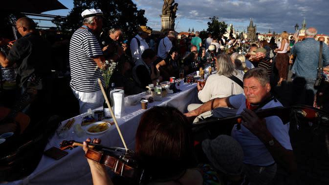 Warga memainkan musik saat makan malam bersama di atas meja sepanjang 500 meter di Charles Bridge di Praha, Republik Ceko, Selasa (30/6/2020). Kegiatan itu merupakan perpisahan simbolis yang digelar untuk menandai akhir dari masa krisis virus corona Covid-19 di negara tersebut. (AP/Petr David Josek)