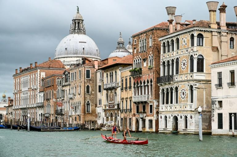 Gondoliers in Venice practise on the Grand Canal as they wait for tourists to return to the city