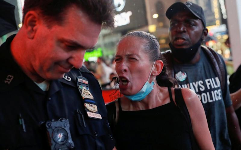 A woman argues with a police officer during a protest in Times Square following the death of black man Daniel Prude, after police put a spit hood over his head during an arrest in Rochester - Reuters