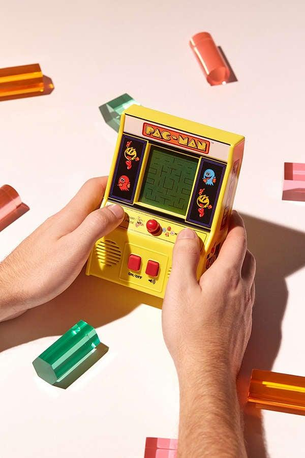 "<p>We have a feeling they're going to obsess over this <a rel=""nofollow"" href=""https://www.popsugar.com/buy/Handheld%20Pac-Man%20Arcade%20Game-323726?p_name=Handheld%20Pac-Man%20Arcade%20Game&retailer=urbanoutfitters.com&price=26&evar1=moms%3Aus&evar9=44555480&evar98=https%3A%2F%2Fwww.popsugar.com%2Ffamily%2Fphoto-gallery%2F44555480%2Fimage%2F44556311%2FHandheld-Pac-Man-Arcade-Game&list1=gifts%2Curban%20outfitters%2Choliday%2Cchristmas%2Cgift%20guide%2Cgifts%20for%20men&prop13=api&pdata=1"" rel=""nofollow"" rel=""nofollow"">Handheld Pac-Man Arcade Game</a> ($26). </p>"