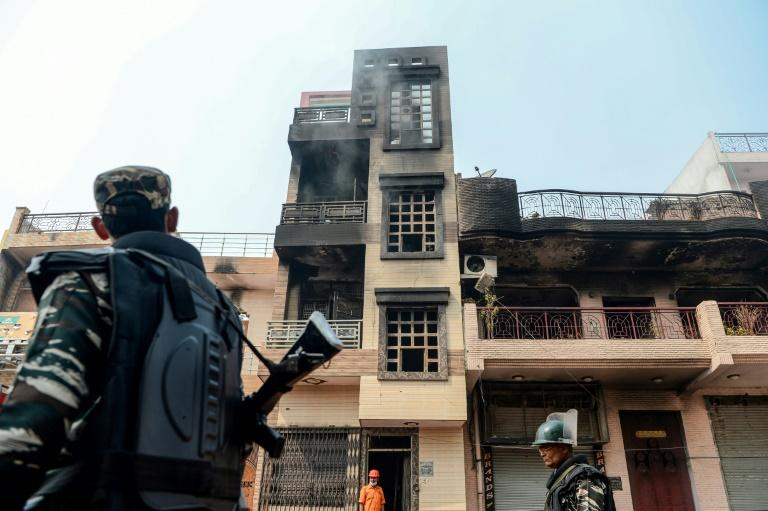Security personnel patrol past burnt-out and damaged residences on February 26 in New Delhi