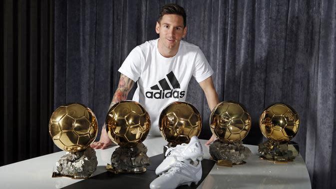 Bintang Barcelona, Lionel Messi, berpose dengan lima trofi Ballon d'Or dan sepatu khusus buatan Adidas.