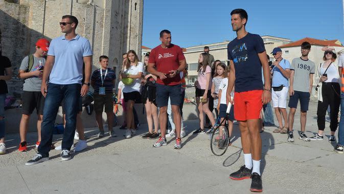Petenis Serbia, Novak Djokovic berbicara kepada para penggemar di Zadar, Kroasia (18/6/2020). Novak Djokovic dinyatakan positif mengidap virus corona covid-19 setelah mengikuti serangkaian pameran tenis yang ia selenggarakan di Serbia dan Kroasia. (AP Photo/Zvonko Kucelin)